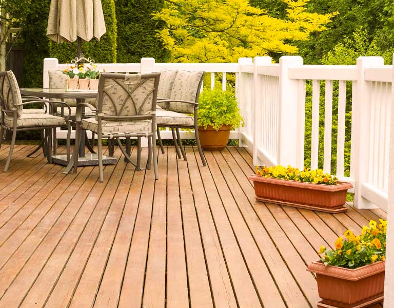 Hardwood deck outdoors with white railing